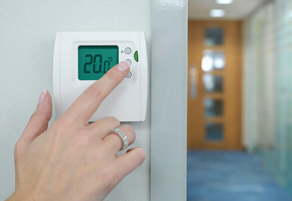 Woman's hand touching a digital thermostat