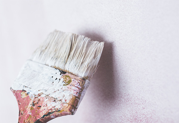 Picture of a brush painting a wall