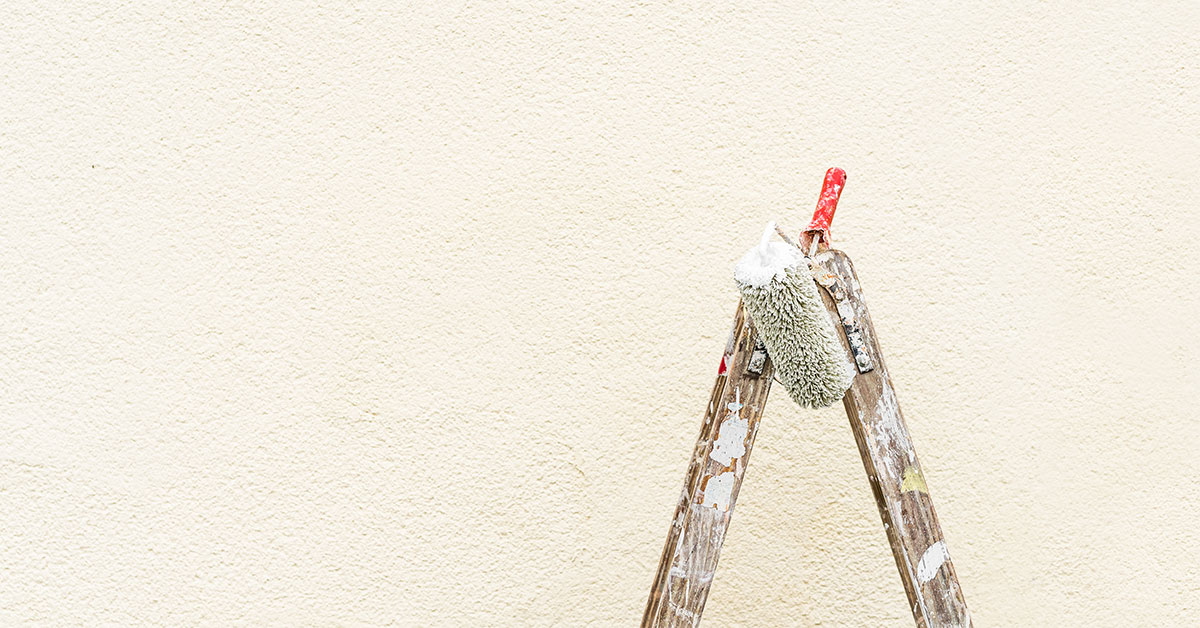 Picture of a ladder and brush on a ladder in front an external wall