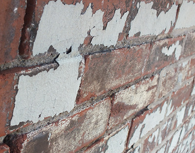 Close up picture of brick wall with old paint